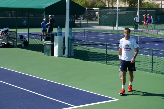 Stepanek in the foreground, coaching for an upcoming women's match going on in the background