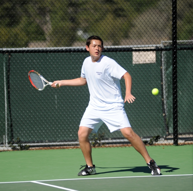 Martin Barnick takes a forehand return in high school tennis competition