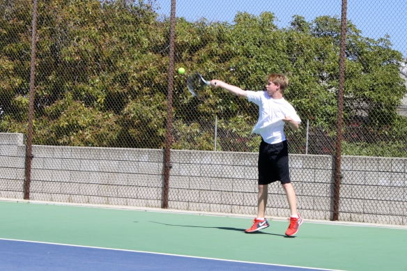 Kylan getting up for the high forehand.